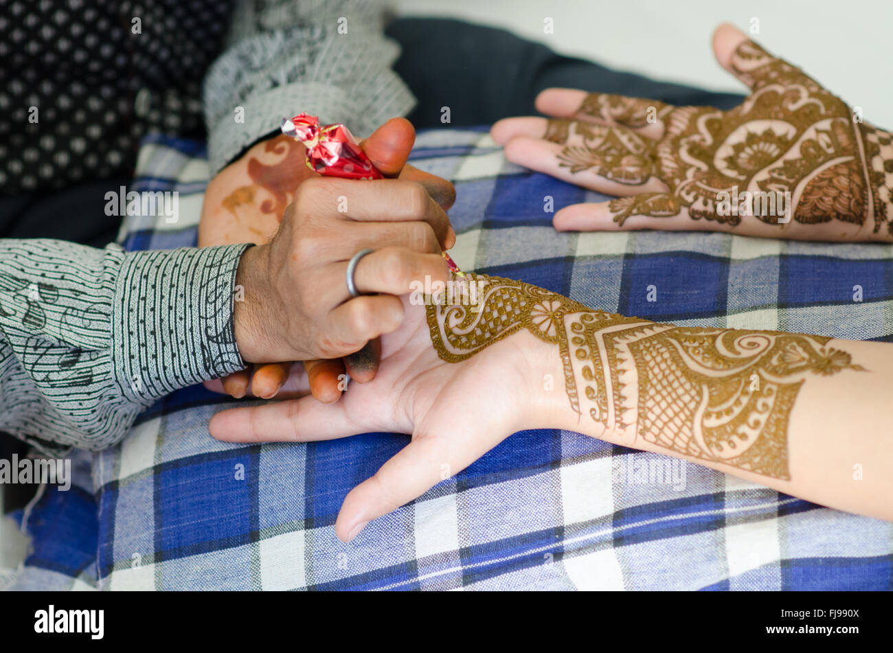Image detail of henna being applied to hand. - Stock Image