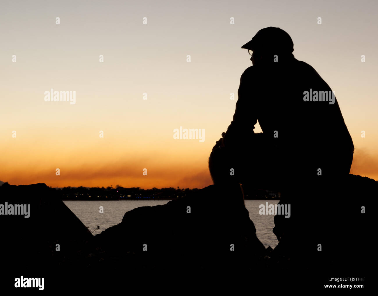 man in silhouette sitting alone watching sunset and contemplating