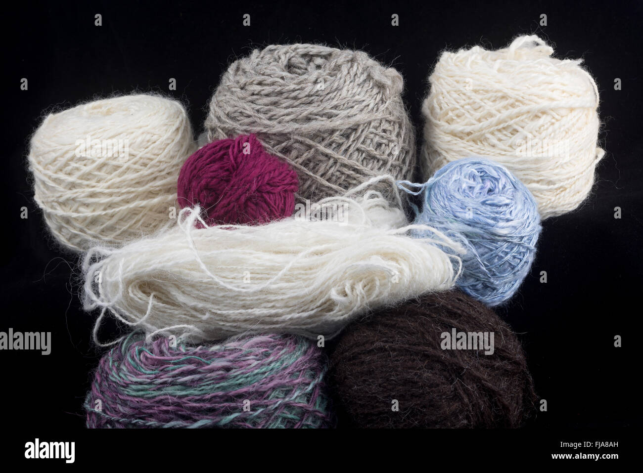 Balls of wool on a black background - Stock Image