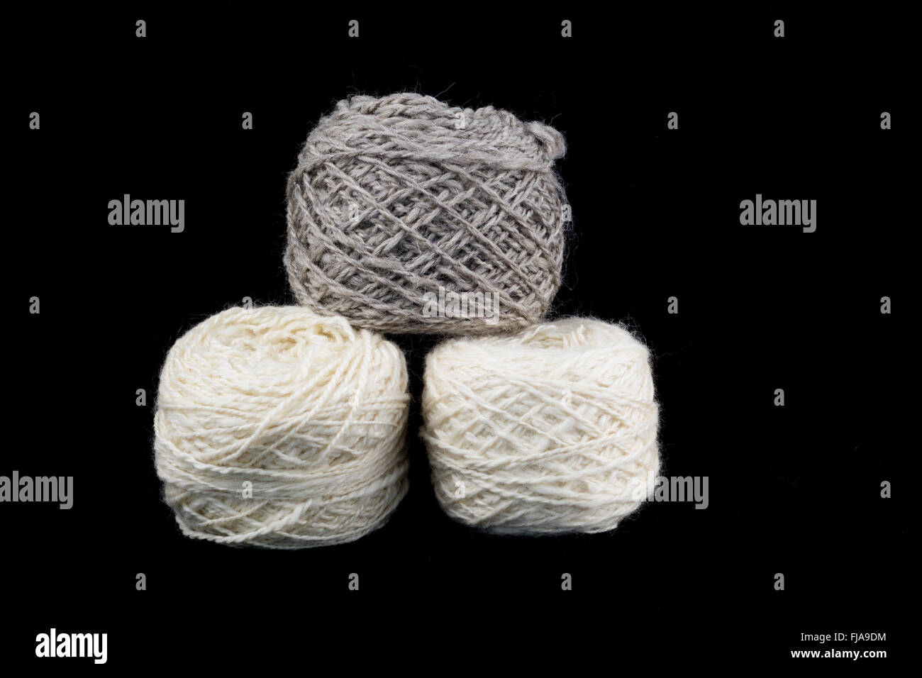Three balls of wool on a black background - Stock Image