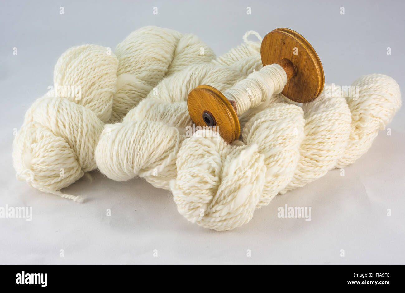 Skeins of wool and bobbin - Stock Image