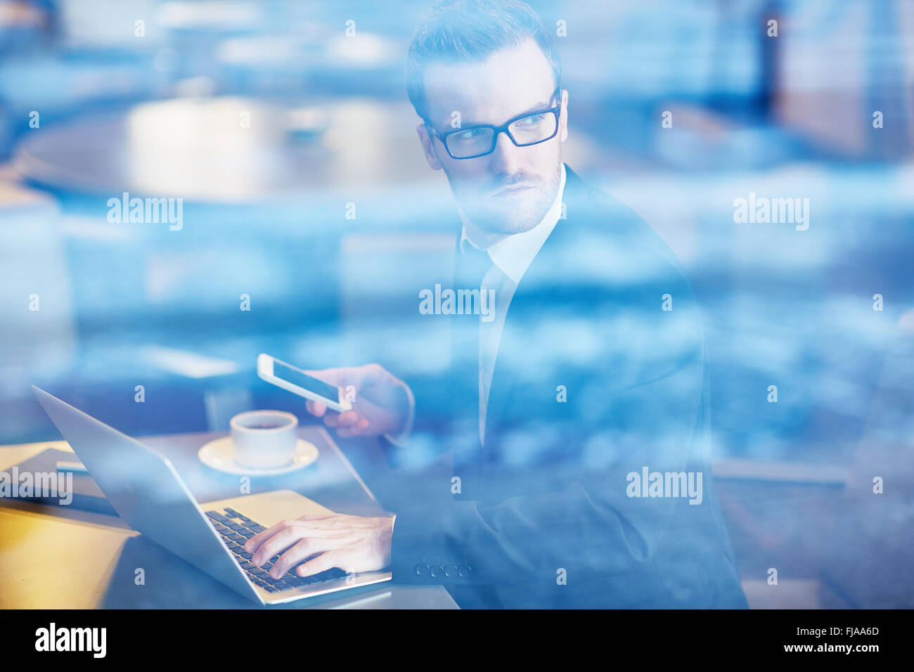 Serious employee with cellphone typing on laptop - Stock Image