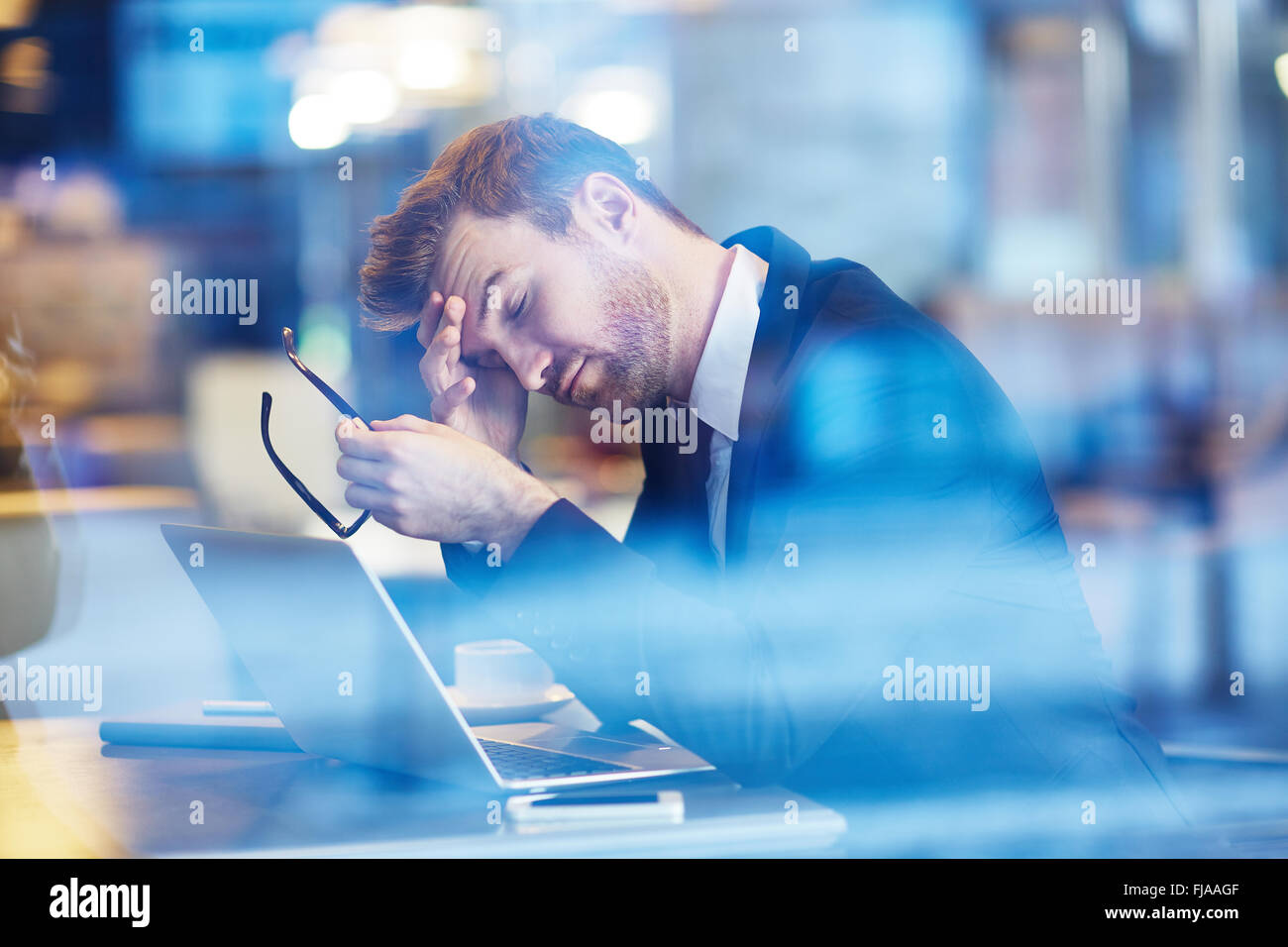 Tired employee touching his forehead - Stock Image