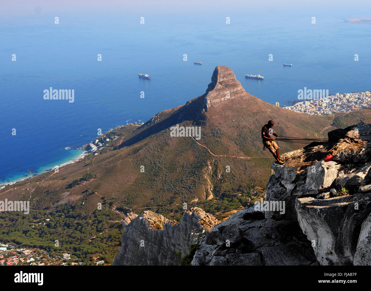 Man preparing to abseil down table mountain in Cape Town, with Lion's Head and the ocean in the background Stock Photo
