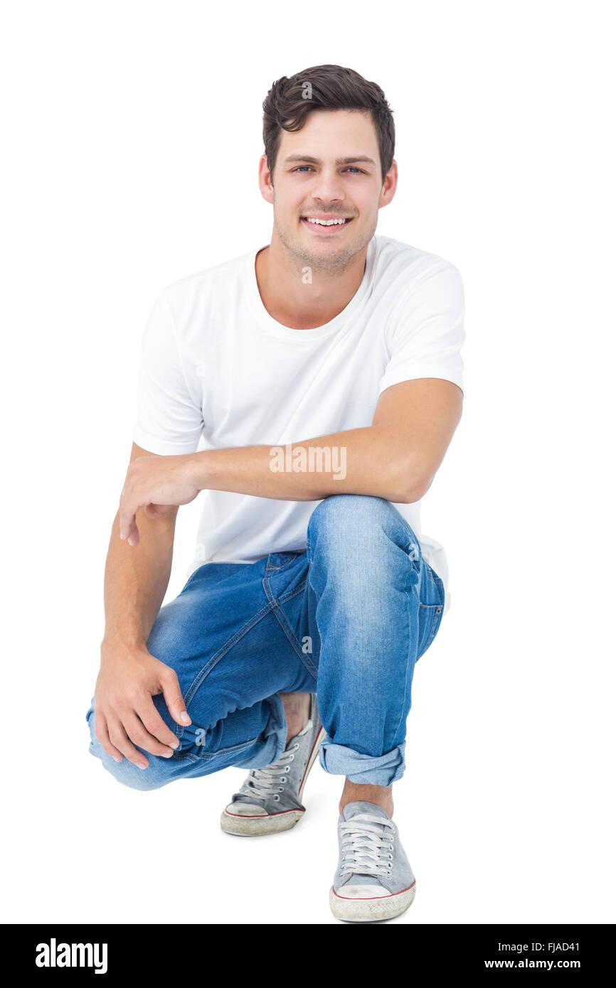 Handsome man crouching - Stock Image