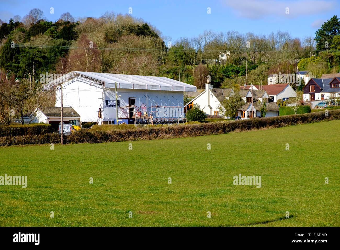 House covered in plastic sheeting while building work is going on. Scaffolding up at house. Rural hamlet Gloucestersire - Stock Image
