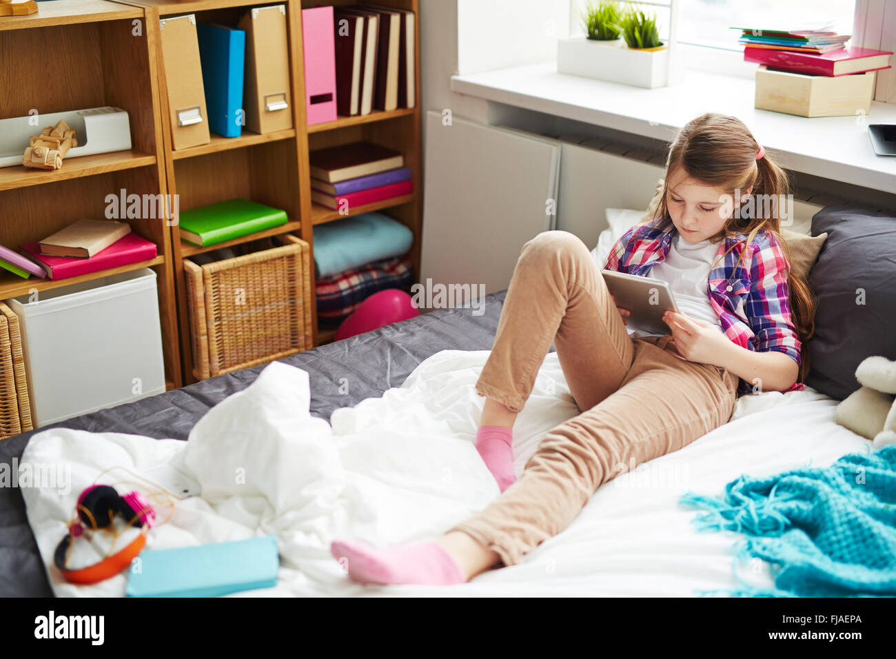 Pretty teenage girl with touchpad networking at home - Stock Image