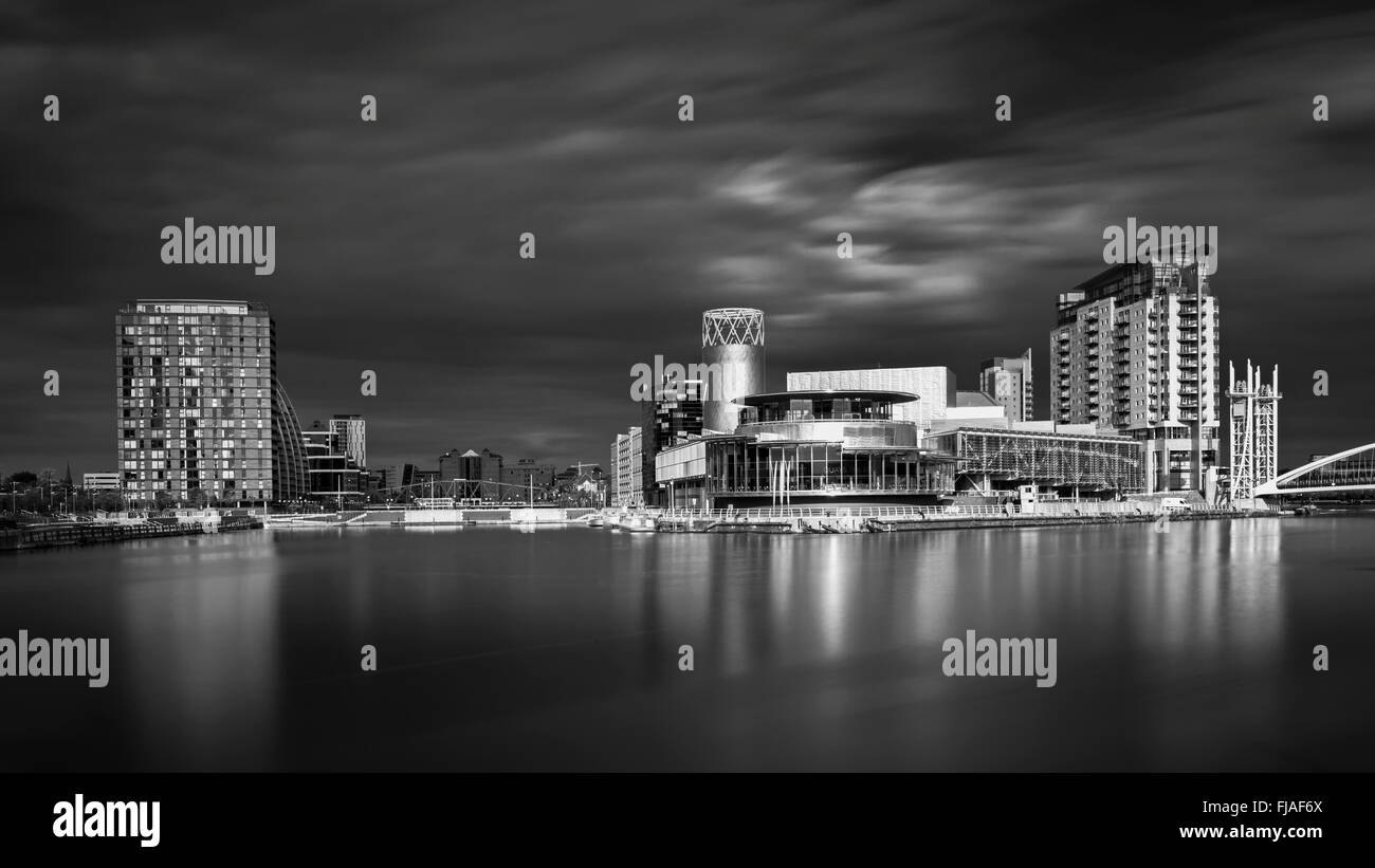 Salford Quays theatre seen across the north bay of the basin. - Stock Image