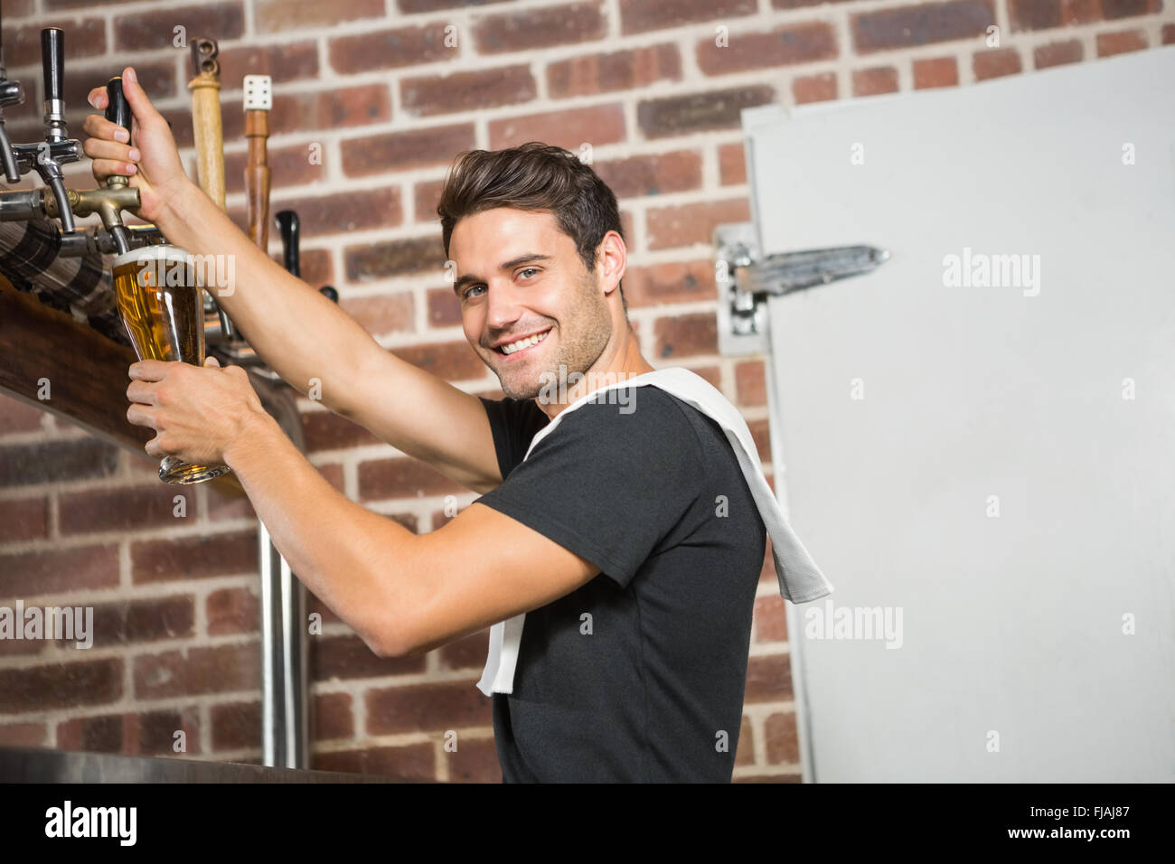 Handsome barman pouring a pint of beer - Stock Image
