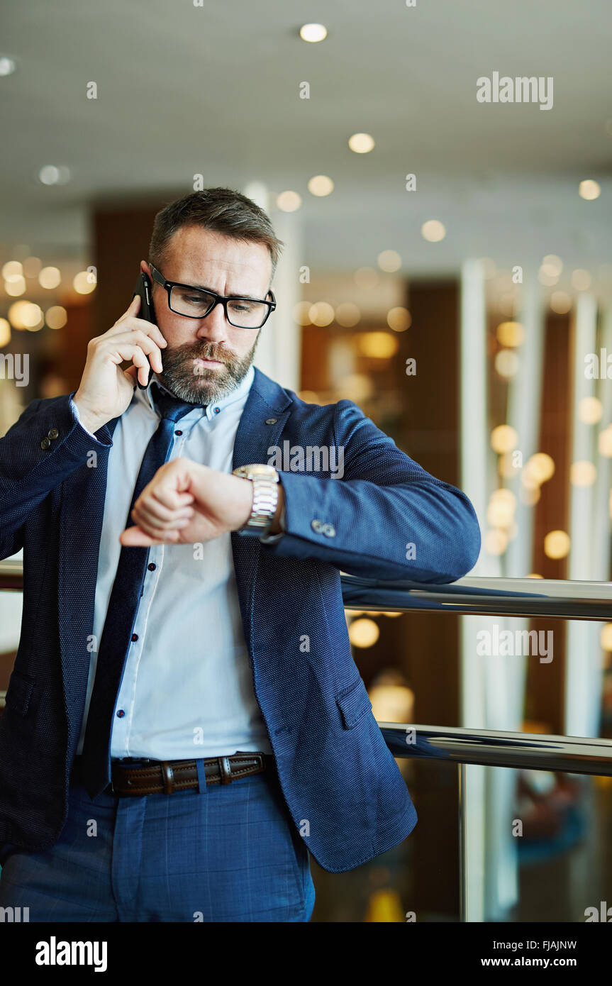 Confident businessman looking at his watch while talking on the phone - Stock Image