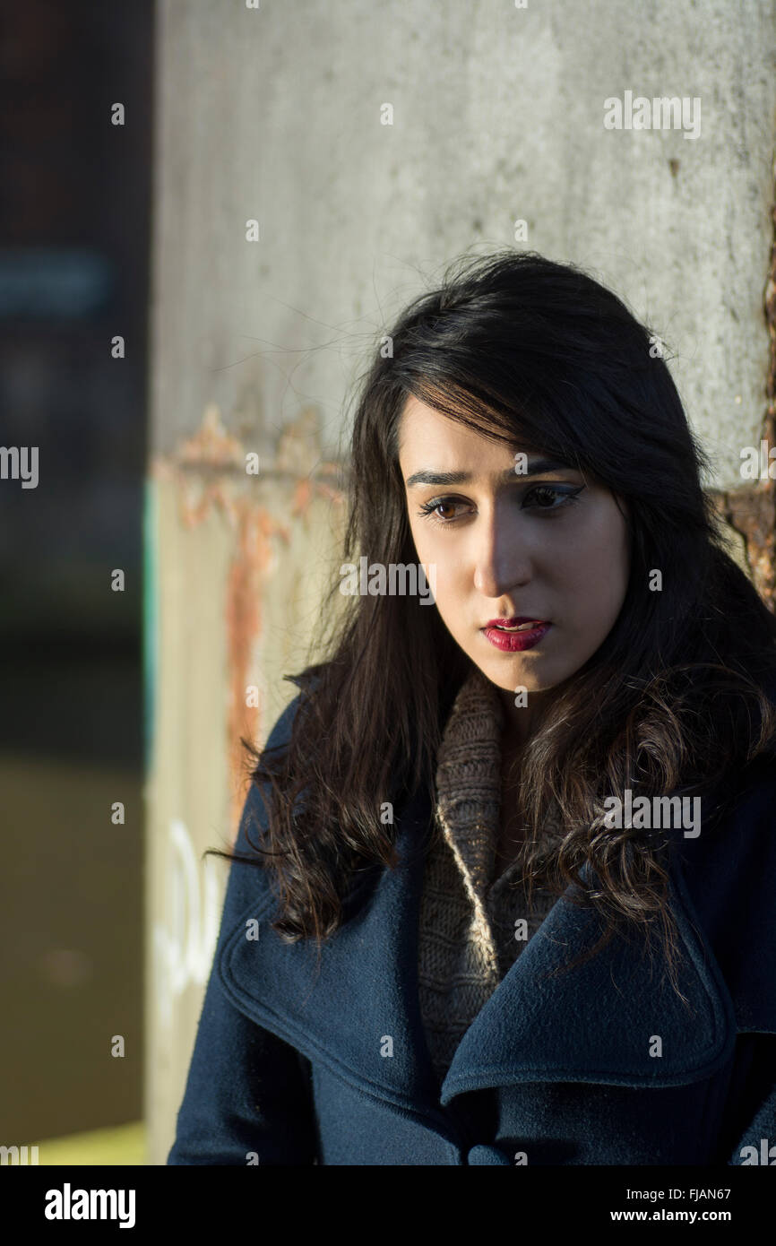 Worried young woman outdoors - Stock Image