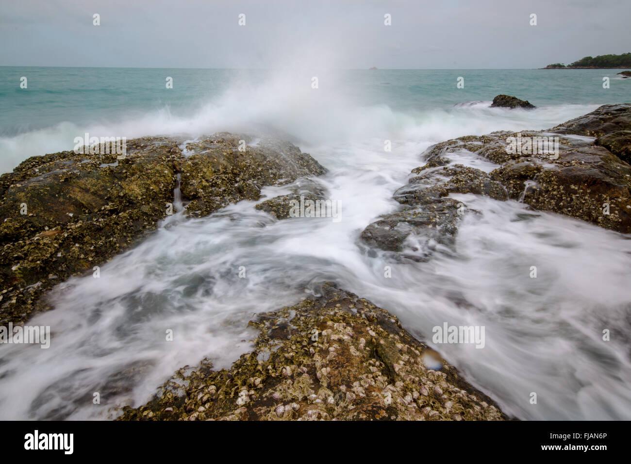 Sea waves crashing to rocks creating foam - Stock Image