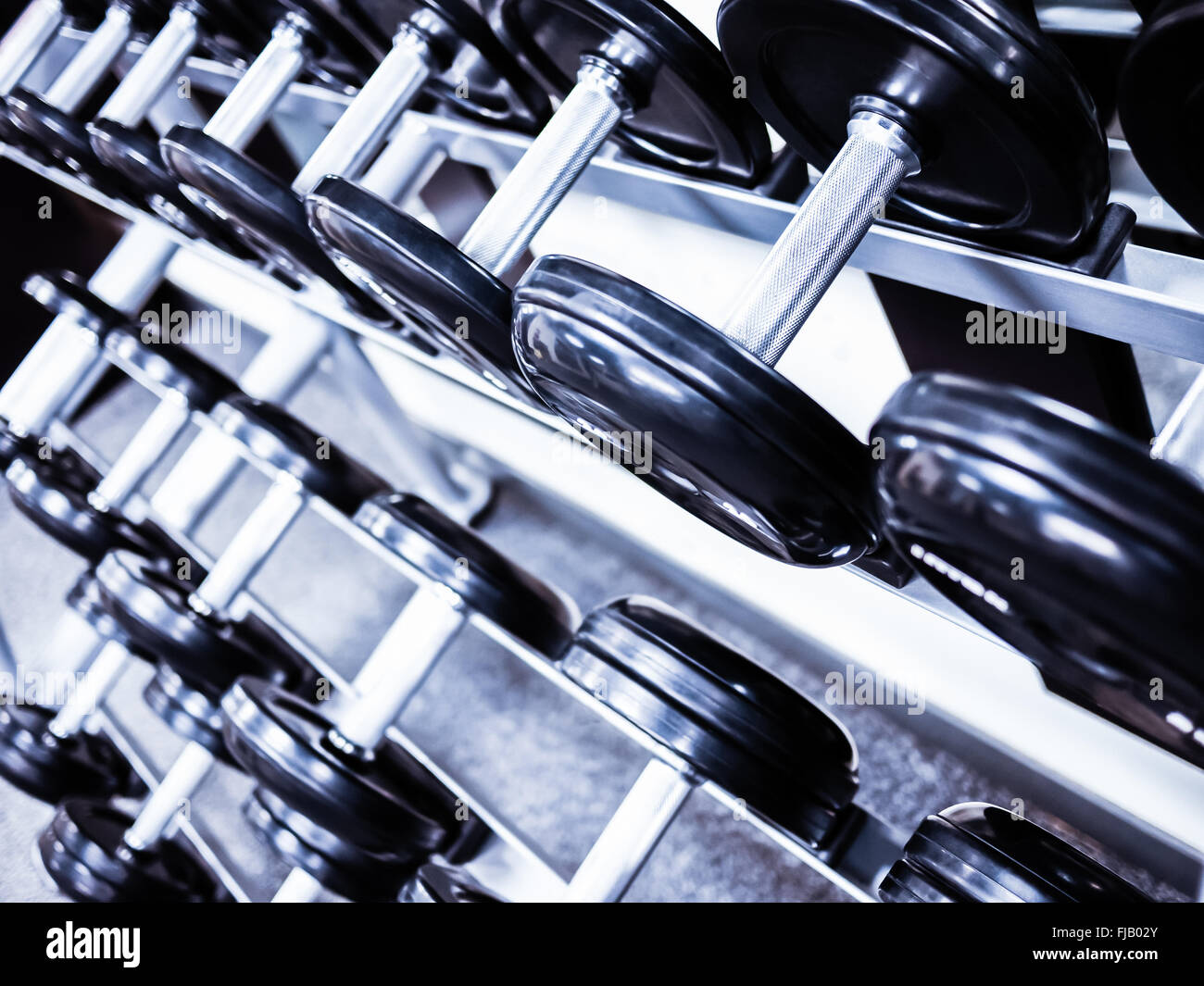 Dumbbell weights on a rack at a healthclub gym - Stock Image