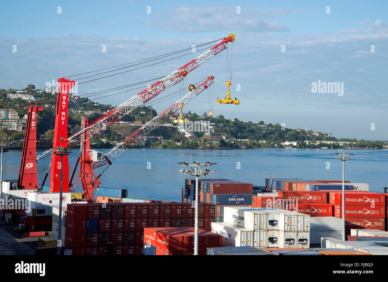 Crane lowers the container down to nautical vessel in Papeete port. - Stock Image