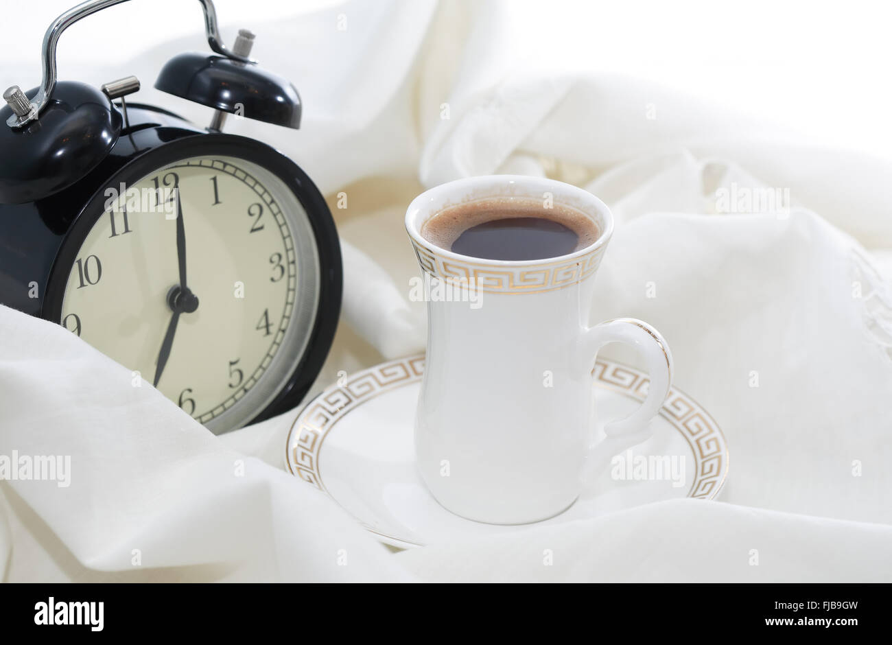 awakening concept alarm clock near cup of coffee on white sheet in