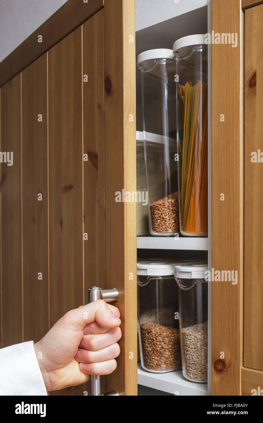man opens the shelf with boxes of pasta and lentils. - Stock Image
