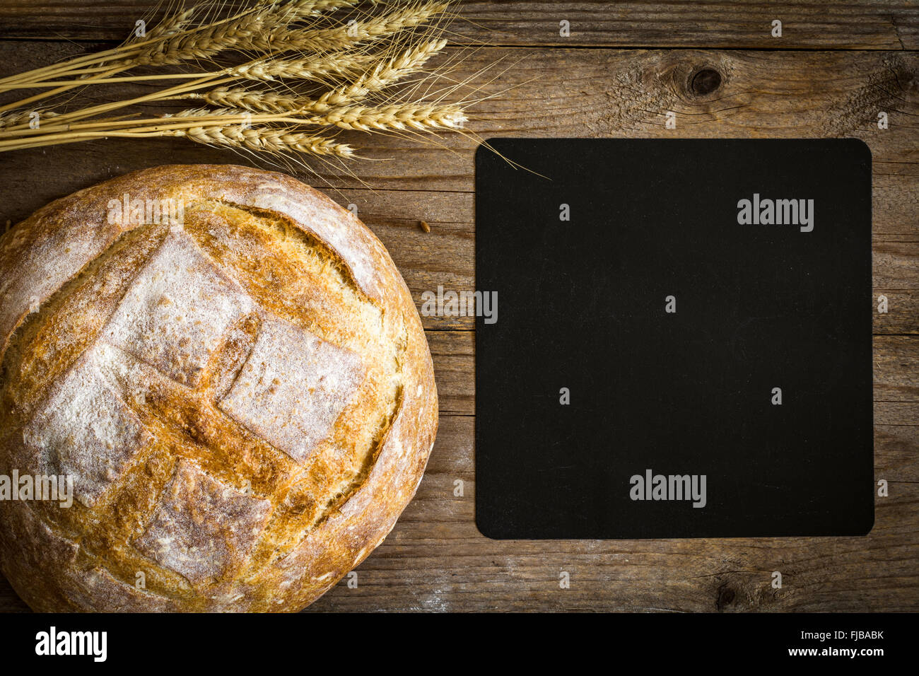Chalkboard, loaf of bread and wheat ears on wooden background, overhead view - Stock Image