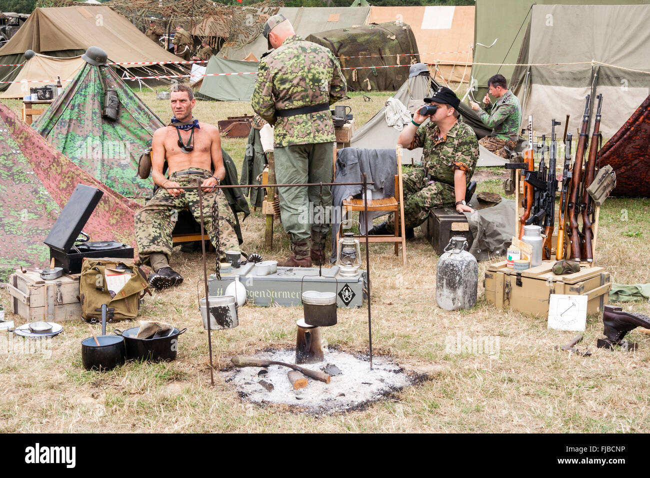 War and Peace Show, England. Second world war re-enactment. German soldiers sitting relaxing with food cooking over - Stock Image