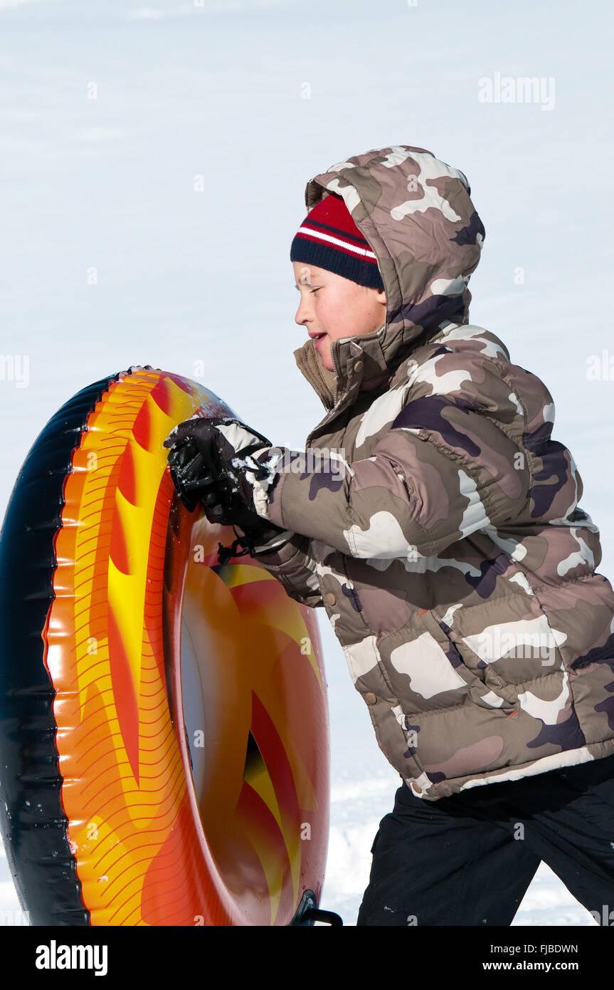 ac8de895c Cute boy in toboggan and camo coat walking with tube Stock Photo ...