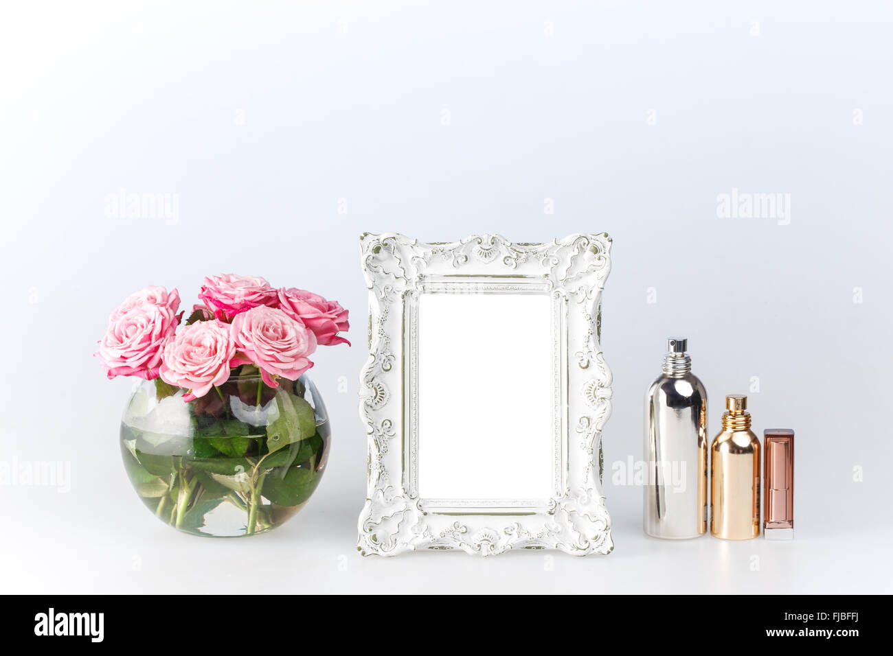 Flowers Vase And Vintage White Picture Frame And Perfume On White