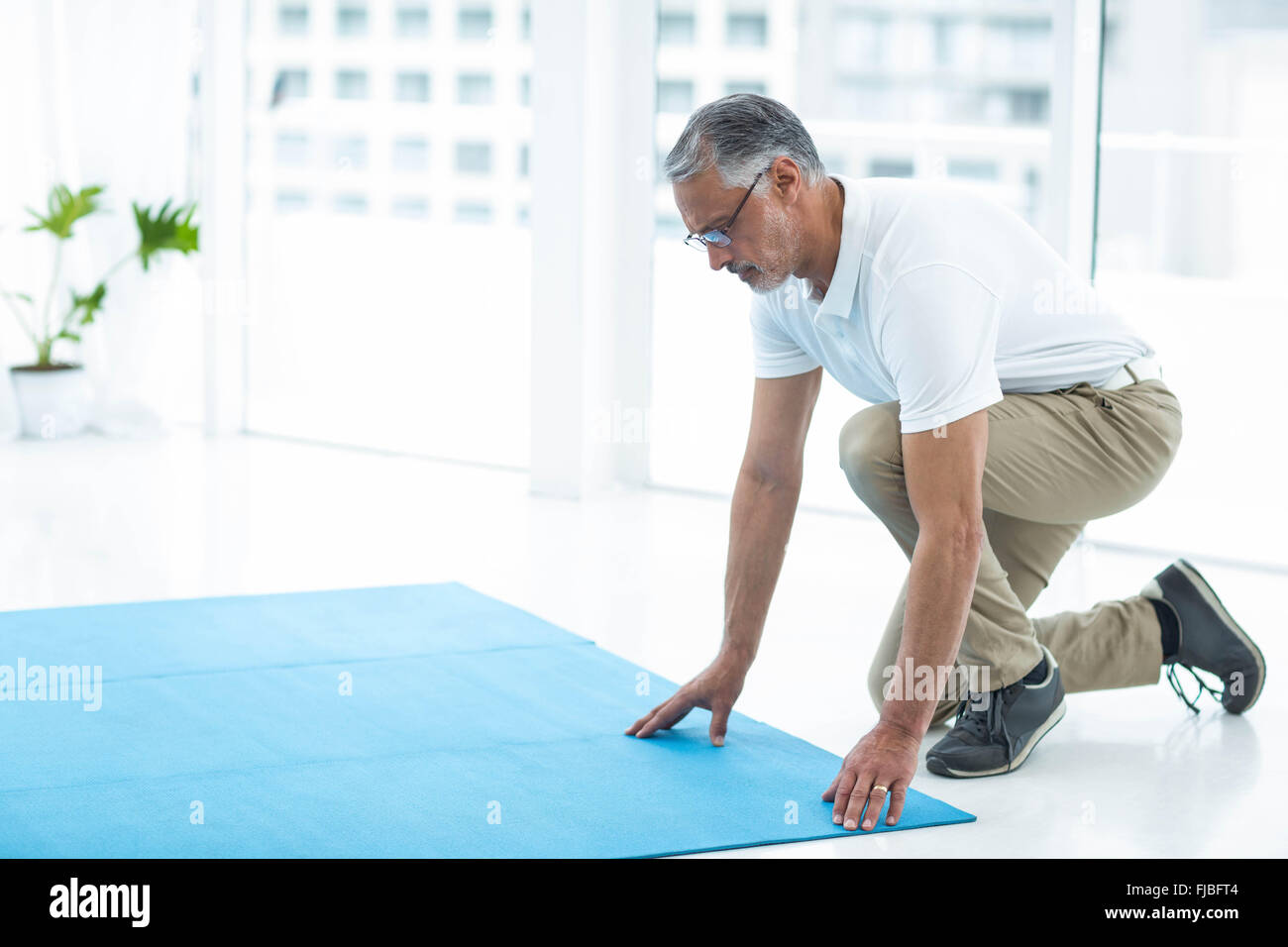 Physiotherapist laying exercise mat - Stock Image