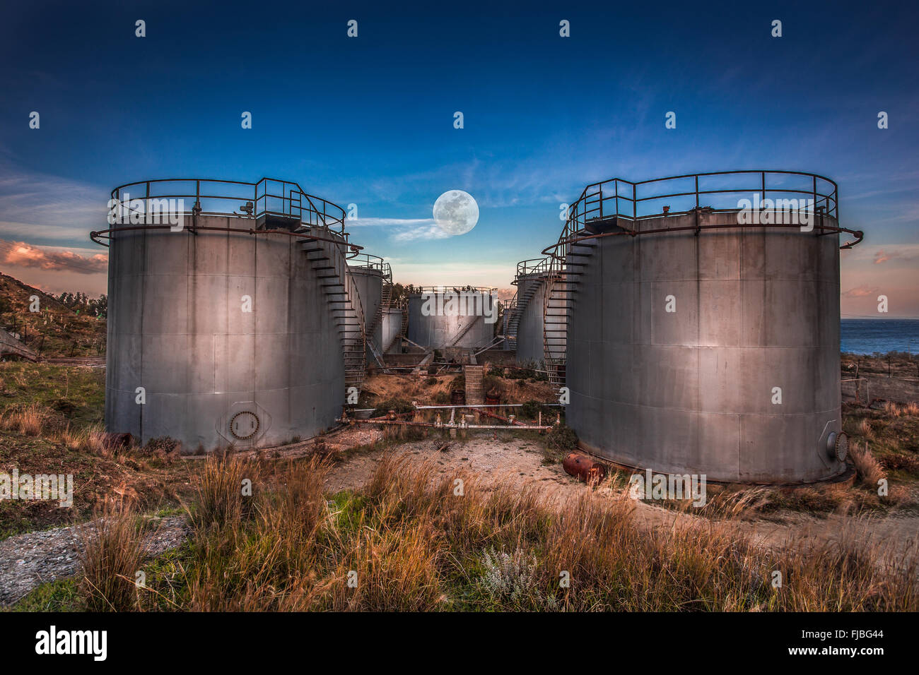 Full moon rising above the old oil refinery - Stock Image