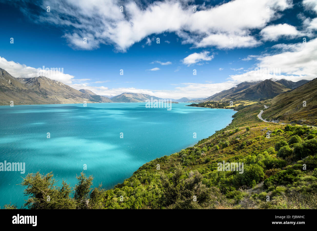 Blue sky with clouds over turquoise lake, Lake Wakatipu, right Glenorchy-Queenstown Road, New Zealand, South Island - Stock Image