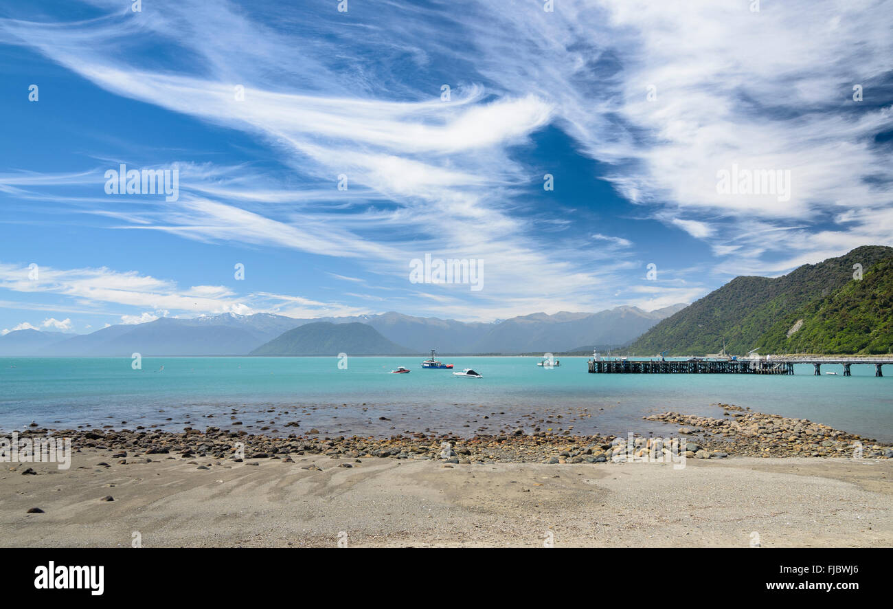 Fishing boat at pier and turquoise sea, cloudy sky, Jackson Bay, West Coast, Tasman, South Island New Zealand - Stock Image