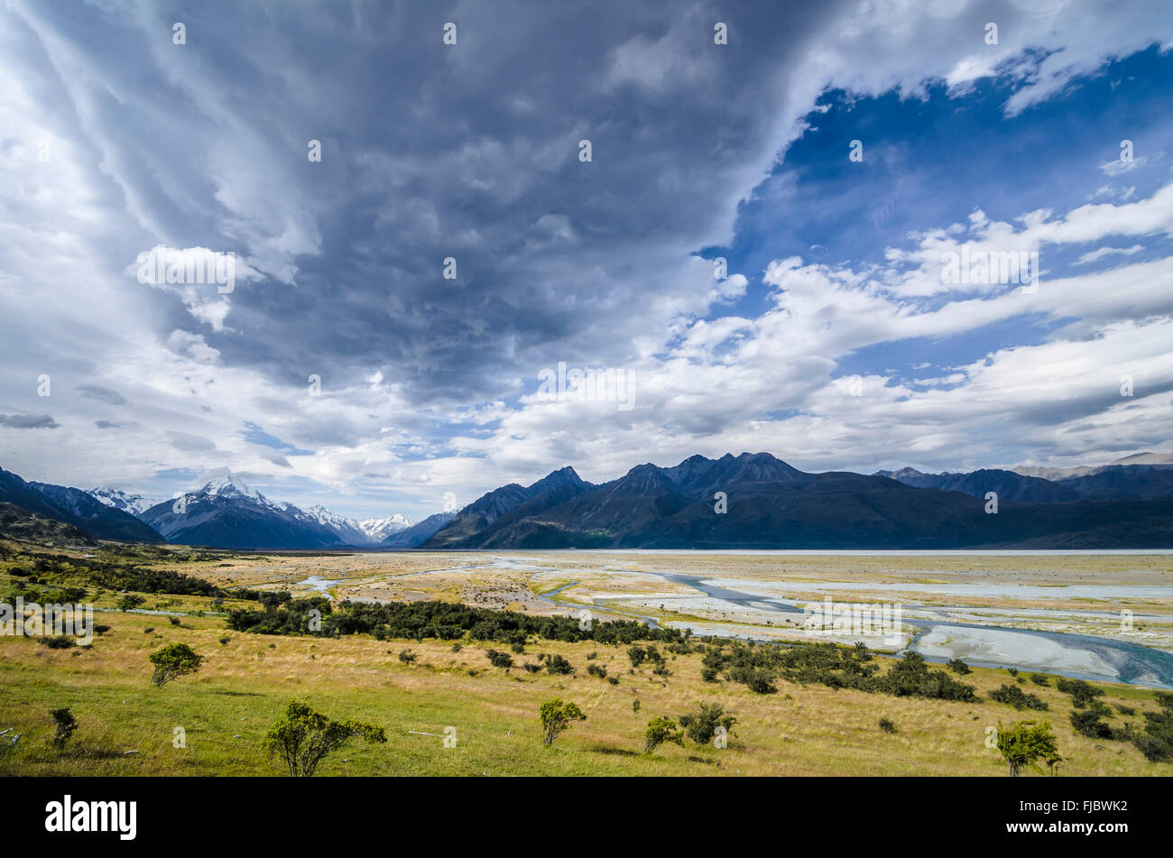 Grassland in front of the wide riverbed of the Tasman River, dramatic clouds, Mount Cook National Park, Pukaki - Stock Image