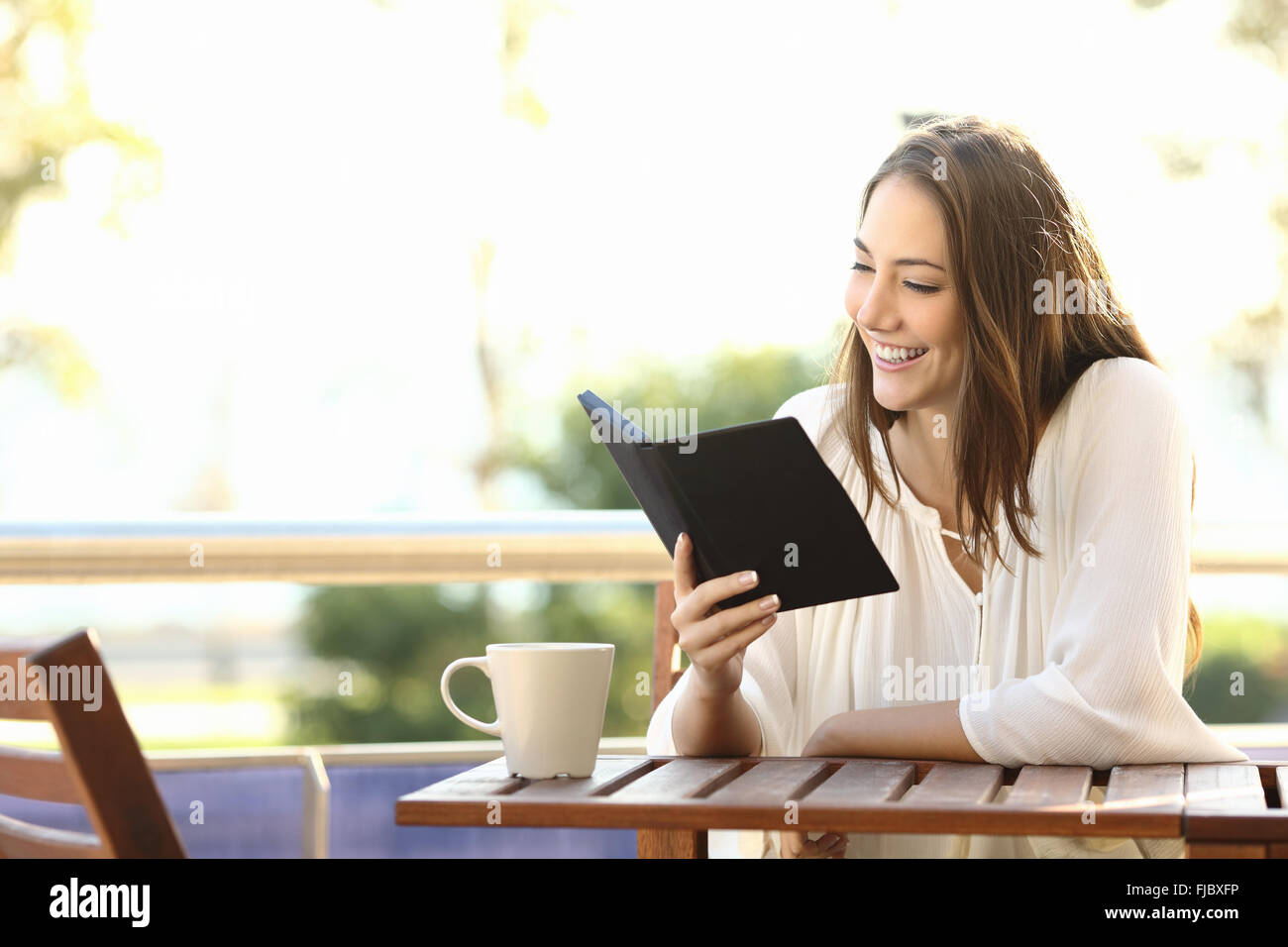 Woman relaxed reading a book in an ebook reader in a bar or at home - Stock Image