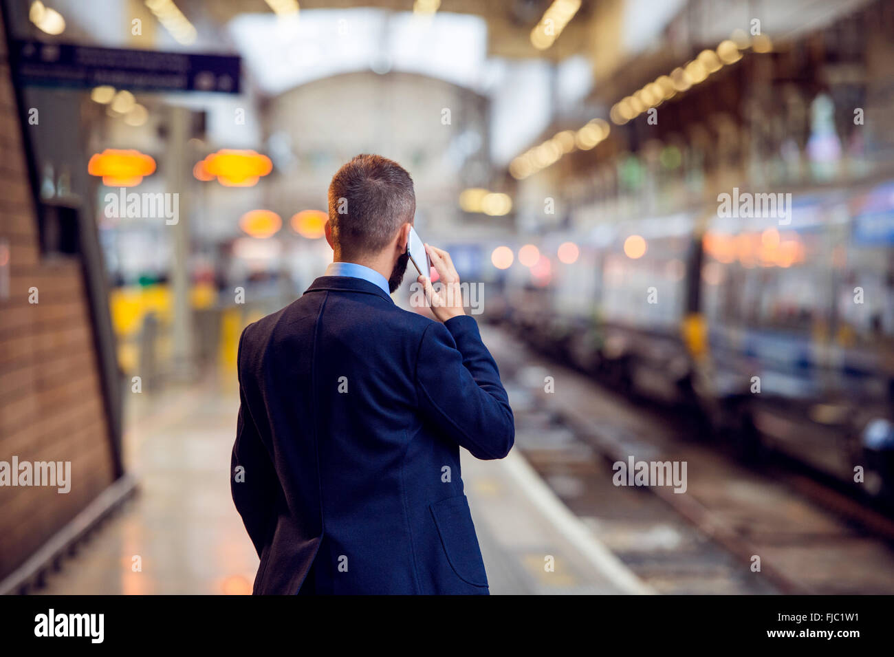 Businessman with smartphone, making a phone call, underground pl - Stock Image