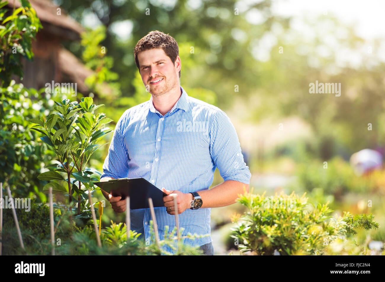 Gardener holding clipboard, in his garden, green sunny nature Stock Photo