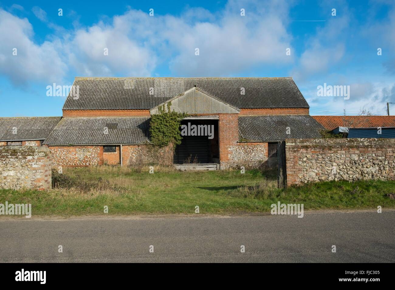 Derelict Flint and red brick  built barn. Agricultural building asbestos roof - Stock Image