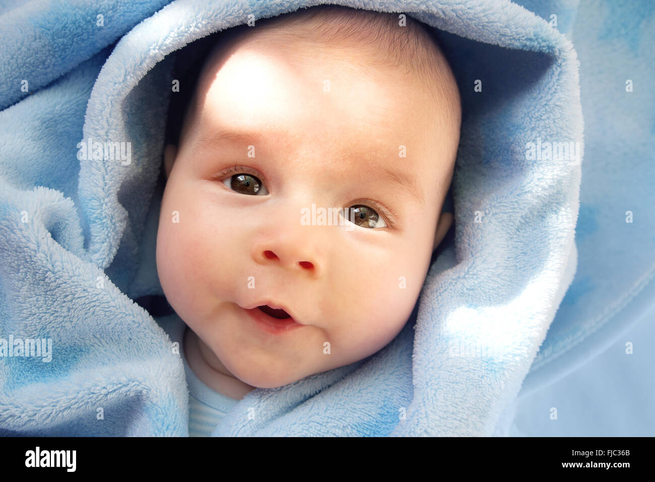 three month old baby wrapped in blue blanket - Stock Image