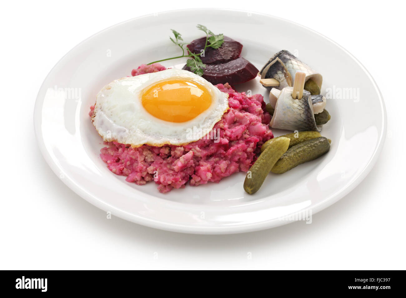 labskaus with fried egg, pickled gherkin, beetroot and rollmops - Stock Image