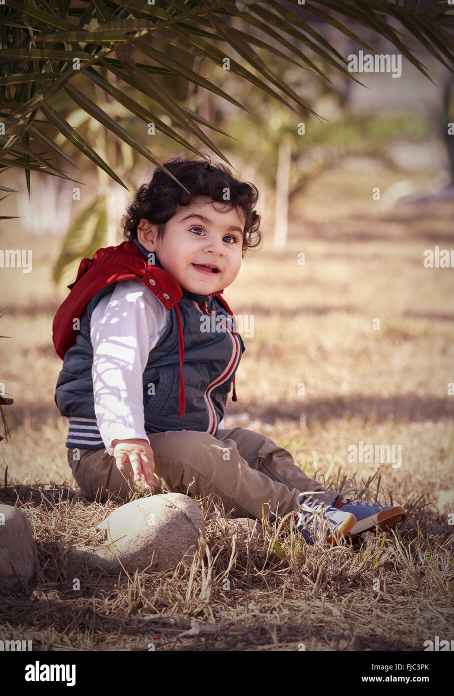 boy wearing warm dry grass under a palm tree - Stock Image