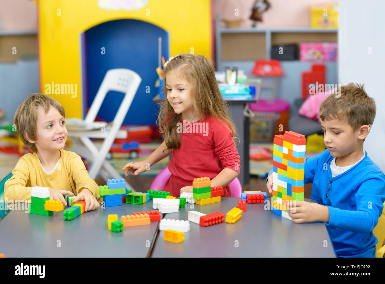Three happy kids playing with plastic building blocks at kindergarten - Stock Image