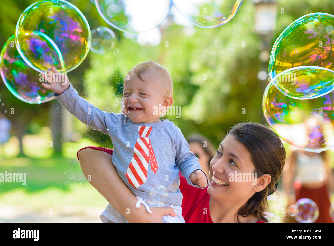 Cute baby and his mother catching soap bubbles in a summer day Stock Photo