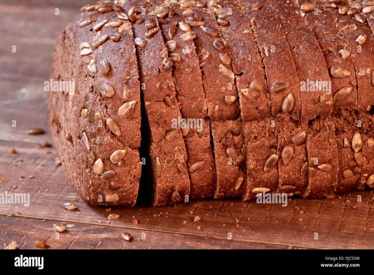 closeup of a sliced loaf of rye bread topped with sunflower seeds on a rustic wooden surface - Stock Image