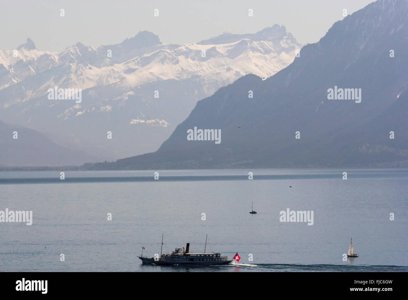 Boat cruising the Lake Geneva with the snowed Alps behind near Lutry, Vaud, Switzerland - Stock Image