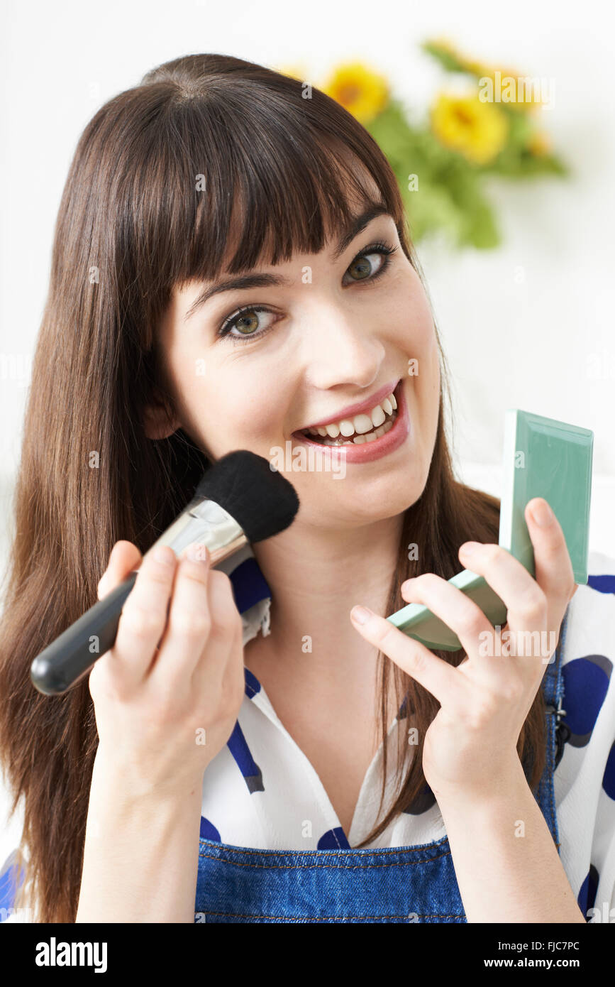 Young Woman Putting On Make Up At Home - Stock Image