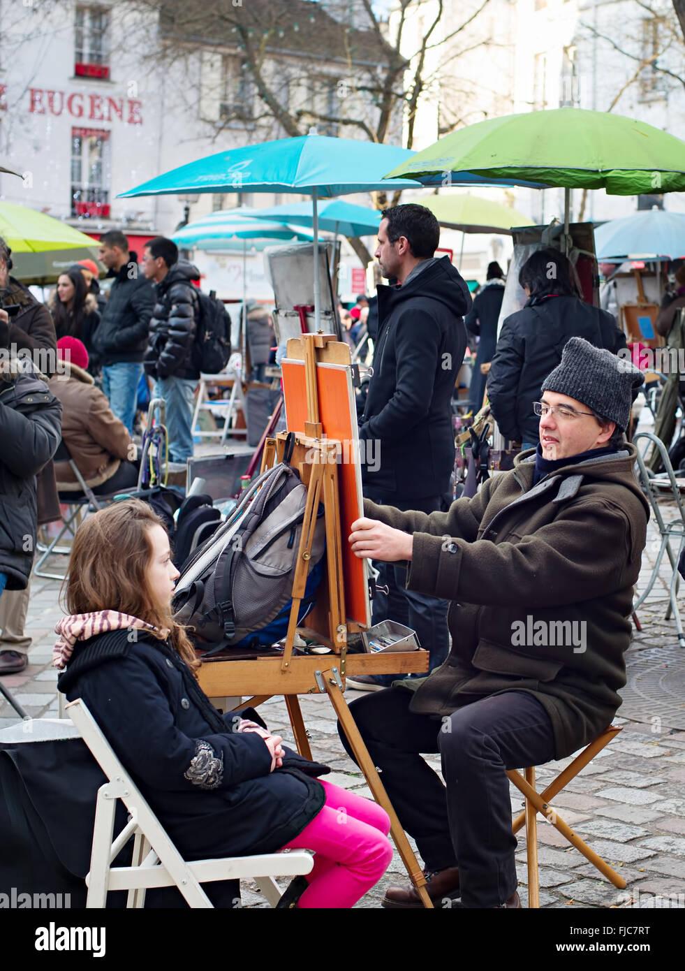Unidentified artist drawing a portrait of the tourist at Place du Tertre, Montmartre. Place du Ter Stock Photo