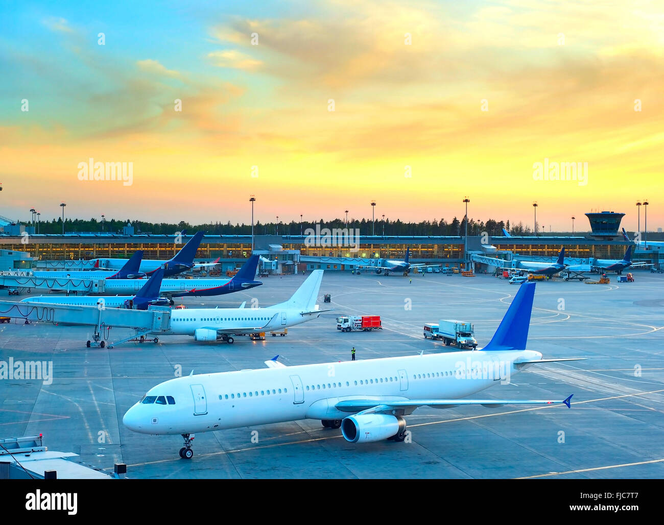 Airplane under loading in an airport at beautiful sunset - Stock Image