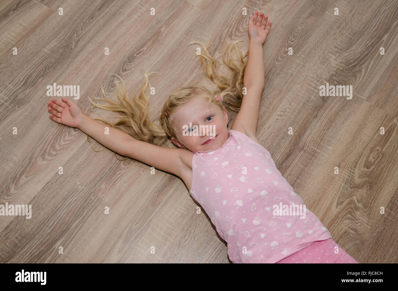 Happy Little Blond Girl Lying On The Ground Stock Photo Alamy