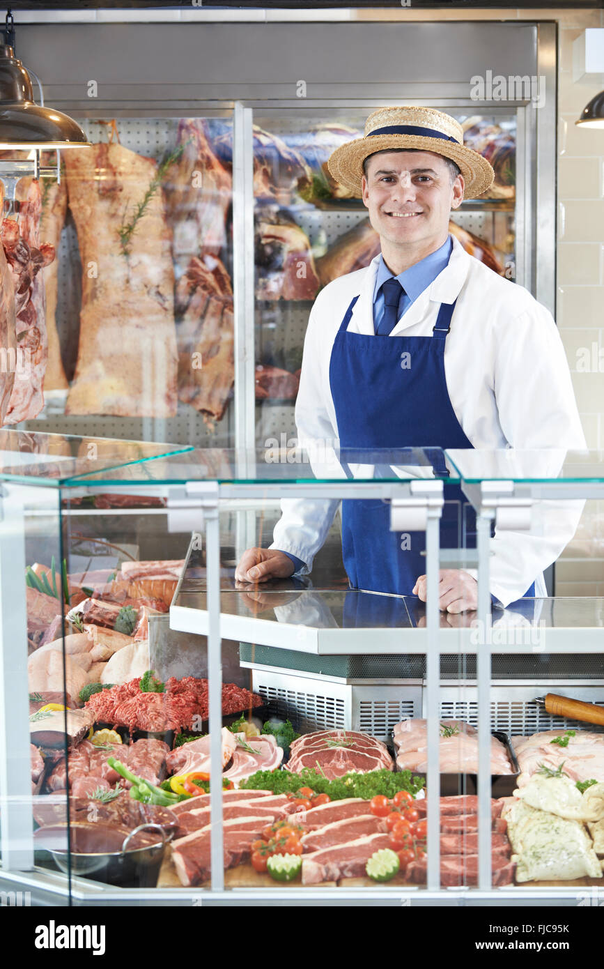 Portrait Of Butcher Standing Behind Counter Stock Photo