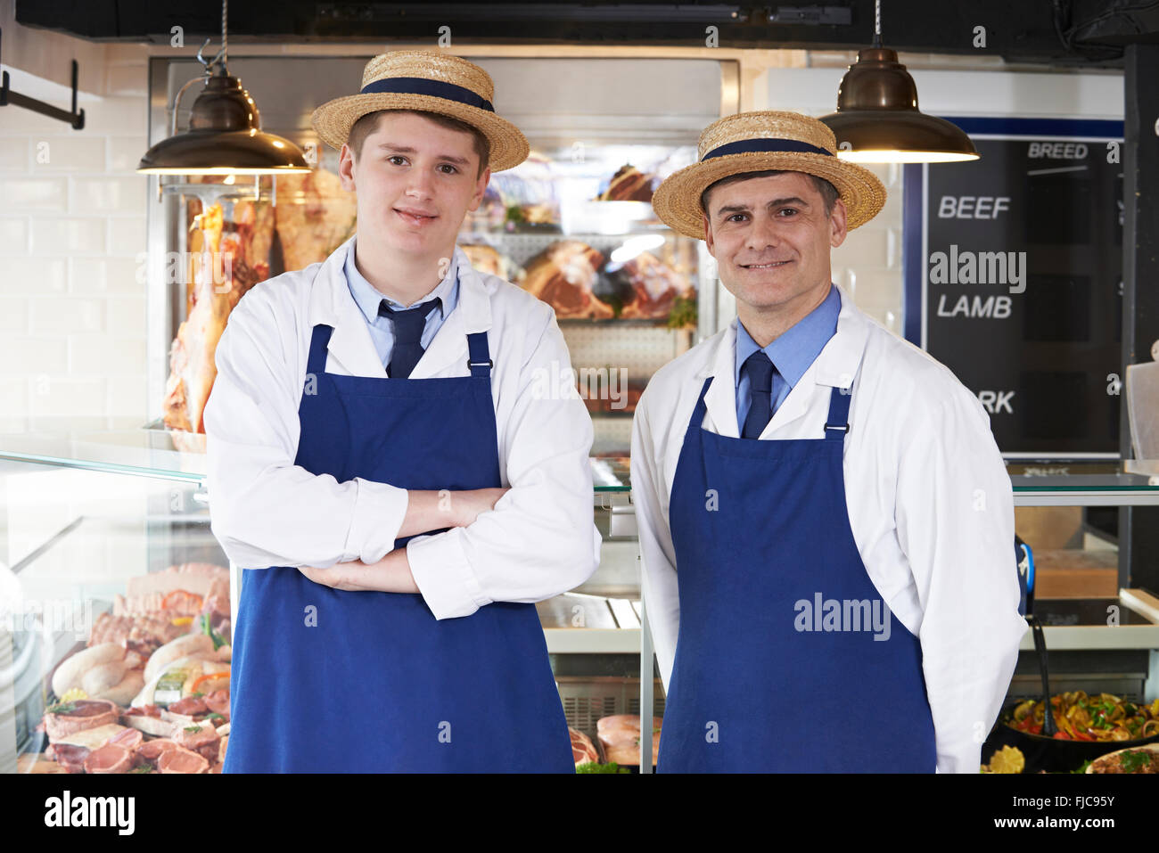 Portrait Of Butcher With Apprentice - Stock Image