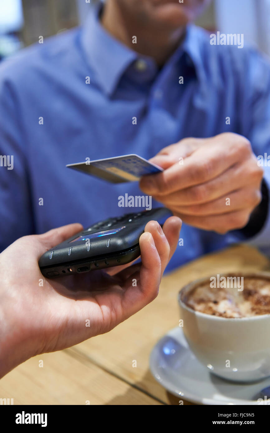 Customer Using Contactless Payment In Coffee Shop - Stock Image
