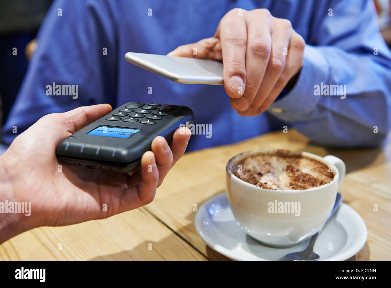 Man Using Contactless Payment App On Mobile Phone In Cafe - Stock Image