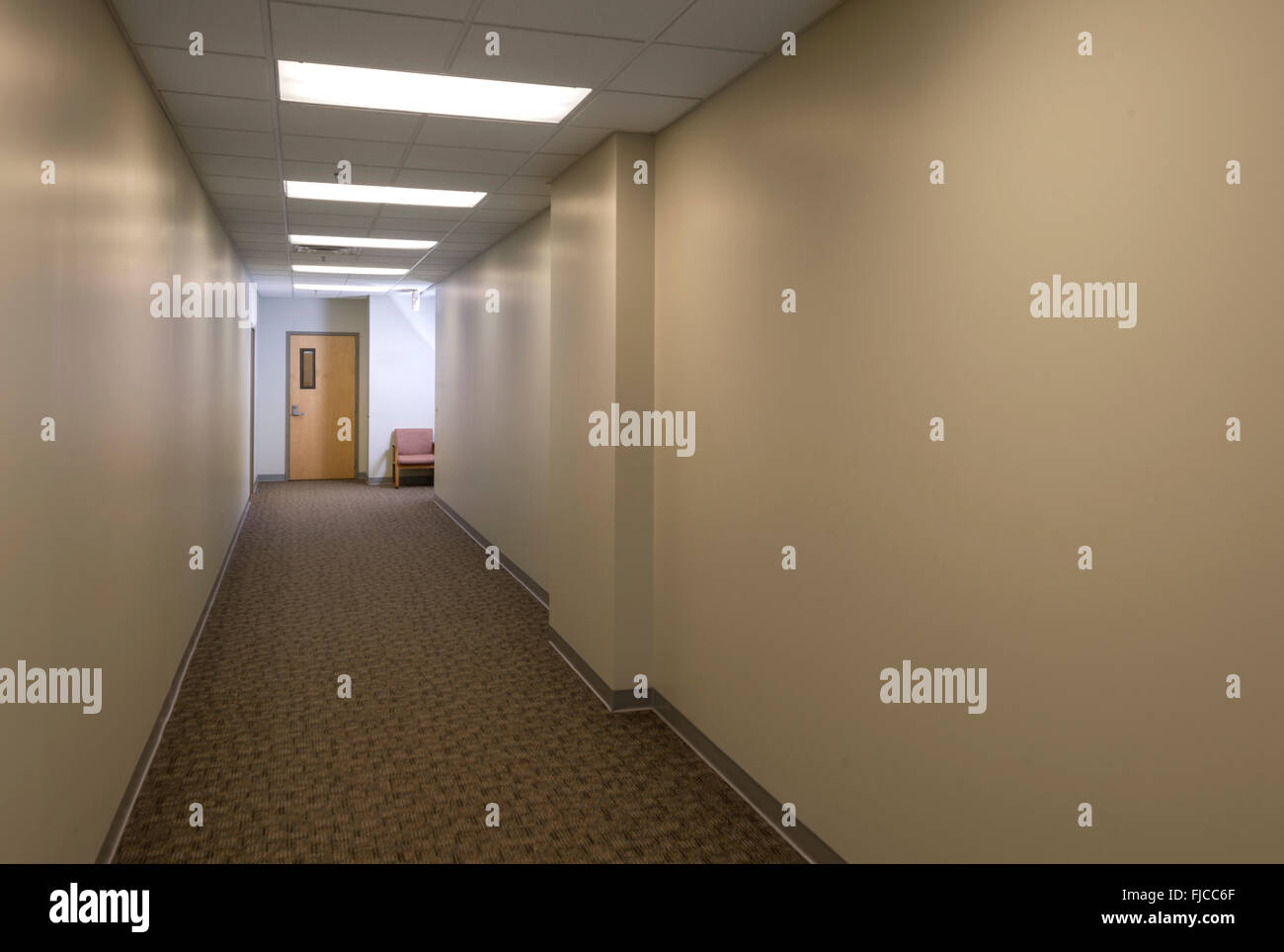 Empty Hallway With Door & Chair At End - Stock Image