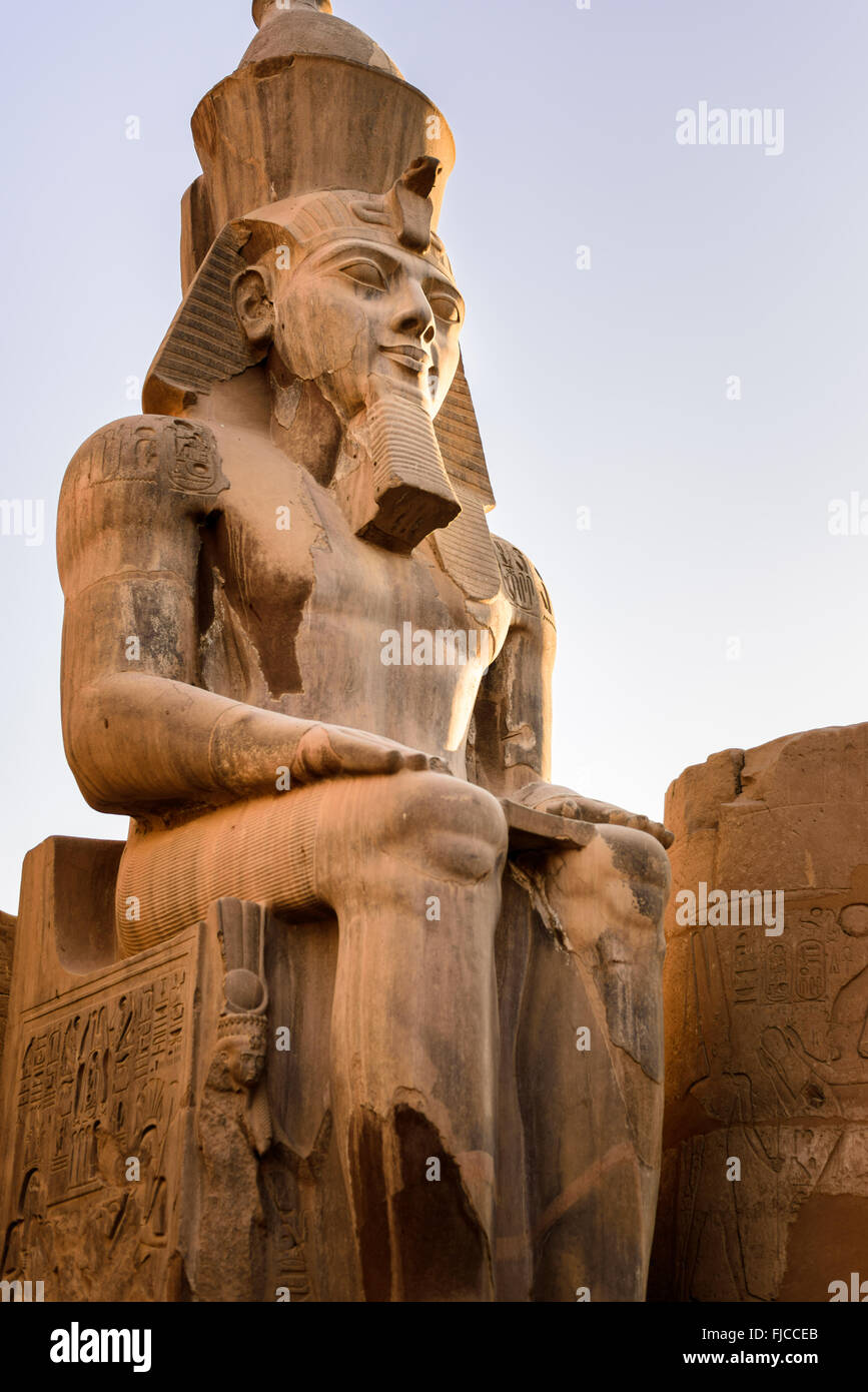 Statue of Ramessess II sitting in front of one of the gates of the Luxor temple. - Stock Image